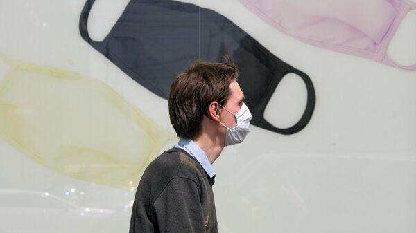 Мужчина в защитной маске на одной из улиц Санкт-Петербурга