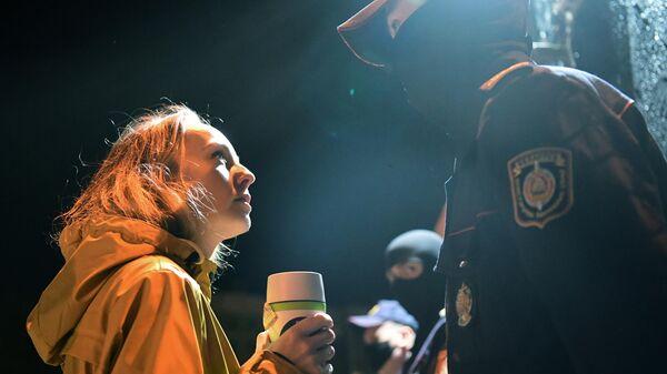Девушка смотрит на сотрудника правоохранительных органов на детской площадке, названой Площадью перемен, на улице Червякова в Минске