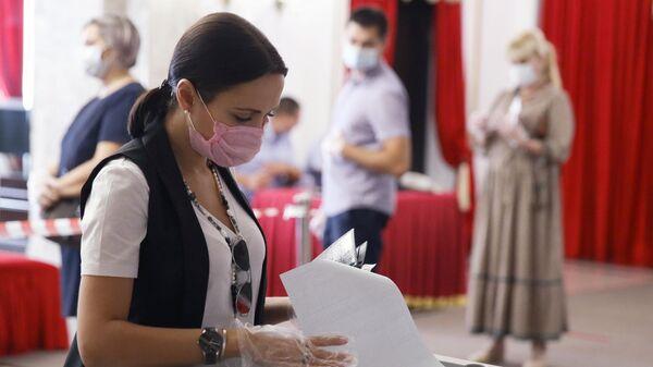 Девушка досрочно голосует на выборах губернатора Краснодарского края на избирательном участке №2010 в Краснодаре