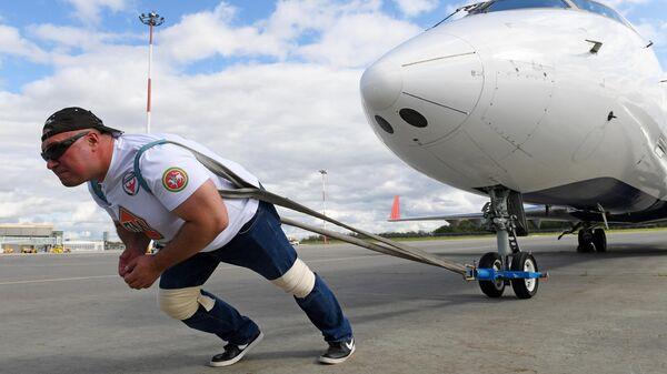 Сергей Агаджанян (Халк) буксирует самолёт Bombardier CRJ200 в международном аэропорту Казань