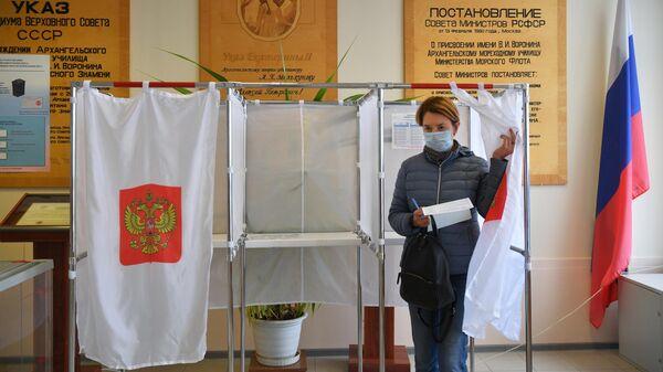 Женщина голосует на выборах