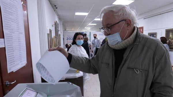 Мужчина голосует в единый день голосования на избирательном участке №524 в Москве