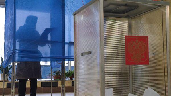 Женщина голосует на избирательном участке в Иркутске на выборах губернатора Иркутской области