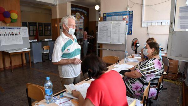 Мужчина и члены избирательной комиссии на избирательном участке, где проходят выборы губернатора Севастополя
