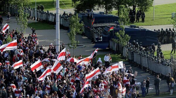 Участники оппозиционного митинга перед сотрудниками правоохранительных органов, перекрывающими улицу, во время протеста против результатов президентских выборов в Минске
