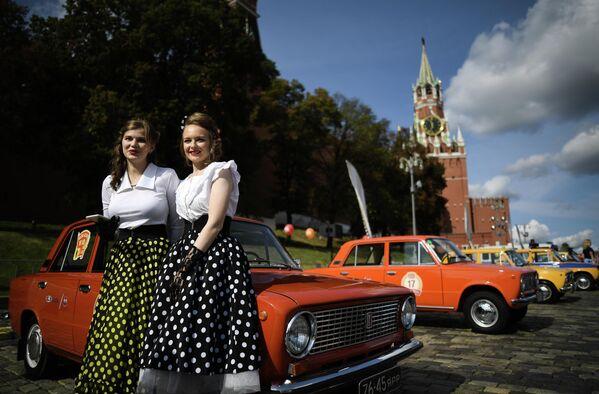 Девушки у автомобиля ВАЗ-21011 перед стартом ежегодного авторалли уникальных машин советской эпохи ГУМ-Авторалли — 2020 на Красной площади в Москве