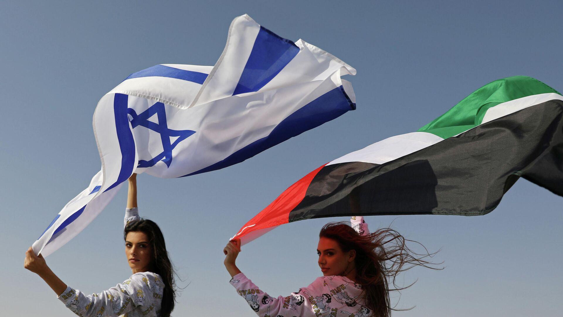 Израильская модель Мэй Тагер с израильским флагом и модель Анастасия с флагом ОАЭ - РИА Новости, 1920, 15.09.2020