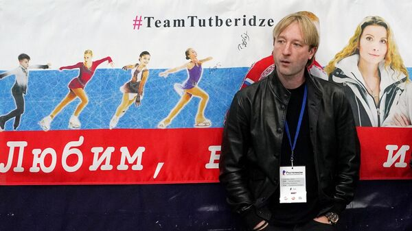 Евгений Плющенко стоит у баннера в поддержку воспитанников команды Этери Тутберидзе