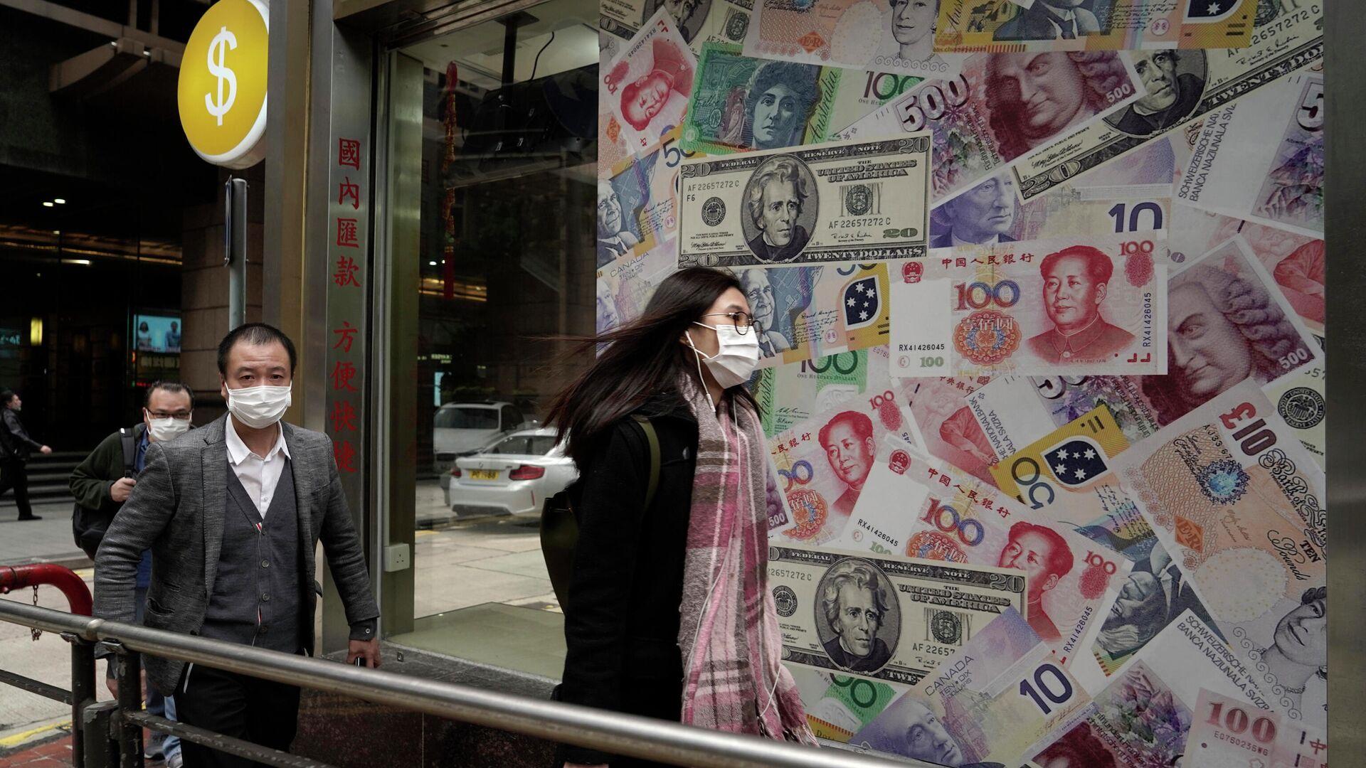 Люди в защитных масках проходят мимо пункта обмена валют в Гонконге - РИА Новости, 1920, 19.09.2020