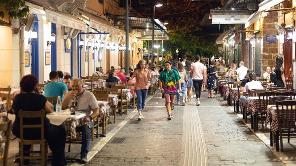 Посетители за столиками летнего кафе в Афинах