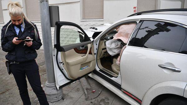Сотрудник правоохранительных органов возле автомобиля Infiniti, пострадавшего в ДТП в центре Москвы