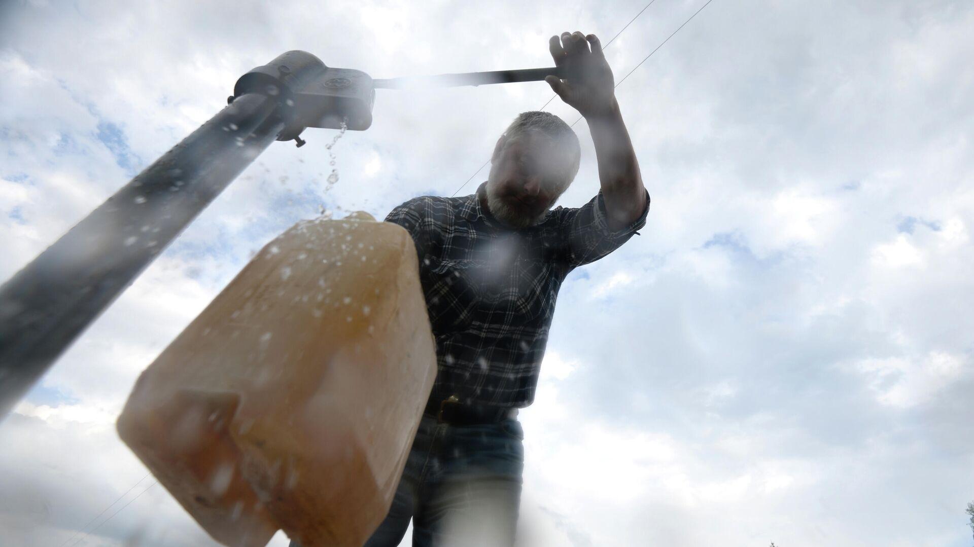 Мужчина набирает воду из колонки - РИА Новости, 1920, 27.12.2020