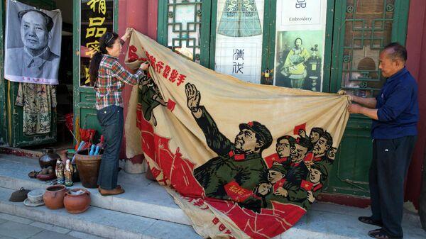 Продавцы разворачивают плакат 1969 года с изображением бывшего китайского лидера Мао Цзэдуна на антикварном рынке в Пекине, Китай