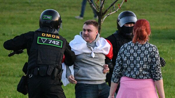 Сотрудники милиции задерживают участника акции протеста в Минске