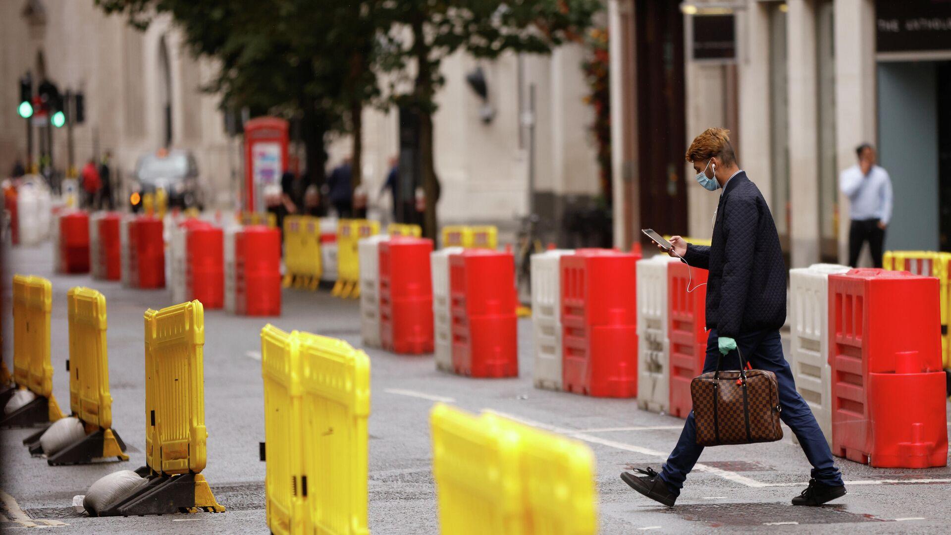 Мужчина в защитной маске переходит дорогу с установленными на ней барьерами для социального дистанцирования в Лондоне - РИА Новости, 1920, 20.10.2020