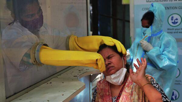 Медицинский работник берет мазок из носа для тестирования на COVID-19 в Хайдарабаде, Индия