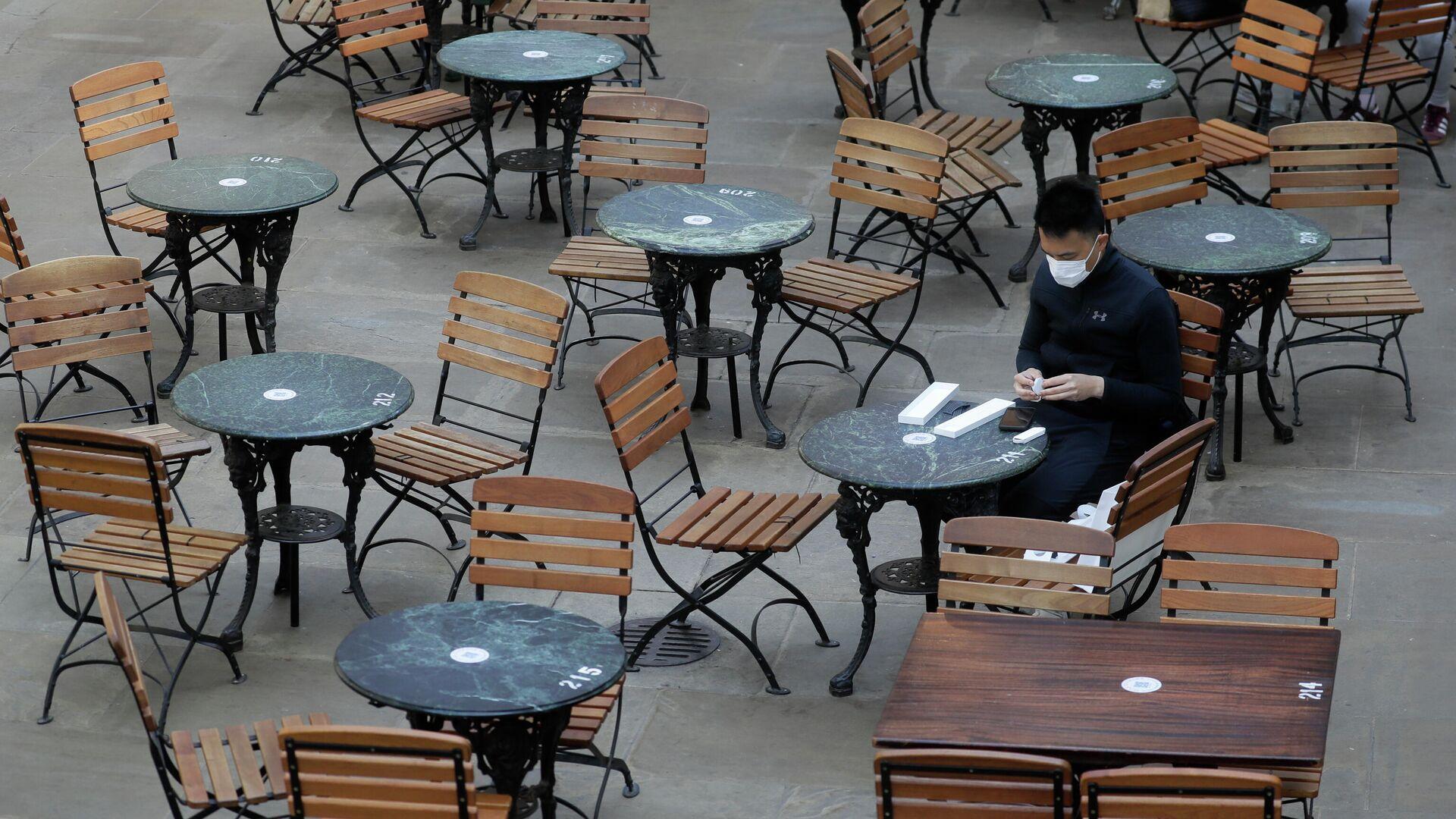 Посетитель за столиком в пустом кафе в Лондоне, Великобритания. 24 сентября 2020 - РИА Новости, 1920, 26.12.2020