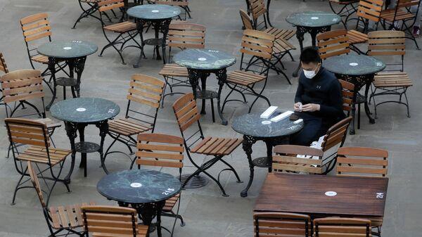 Посетитель за столиком в пустом кафе в Лондоне, Великобритания. 24 сентября 2020