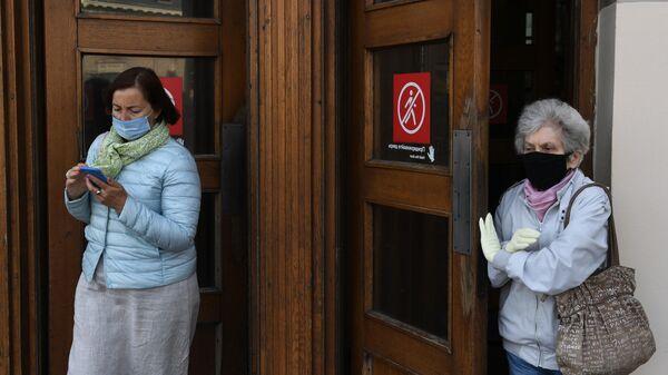 Пассажиры в медицинских масках выходят из вестибюля станции метро Парк культуры в Москве