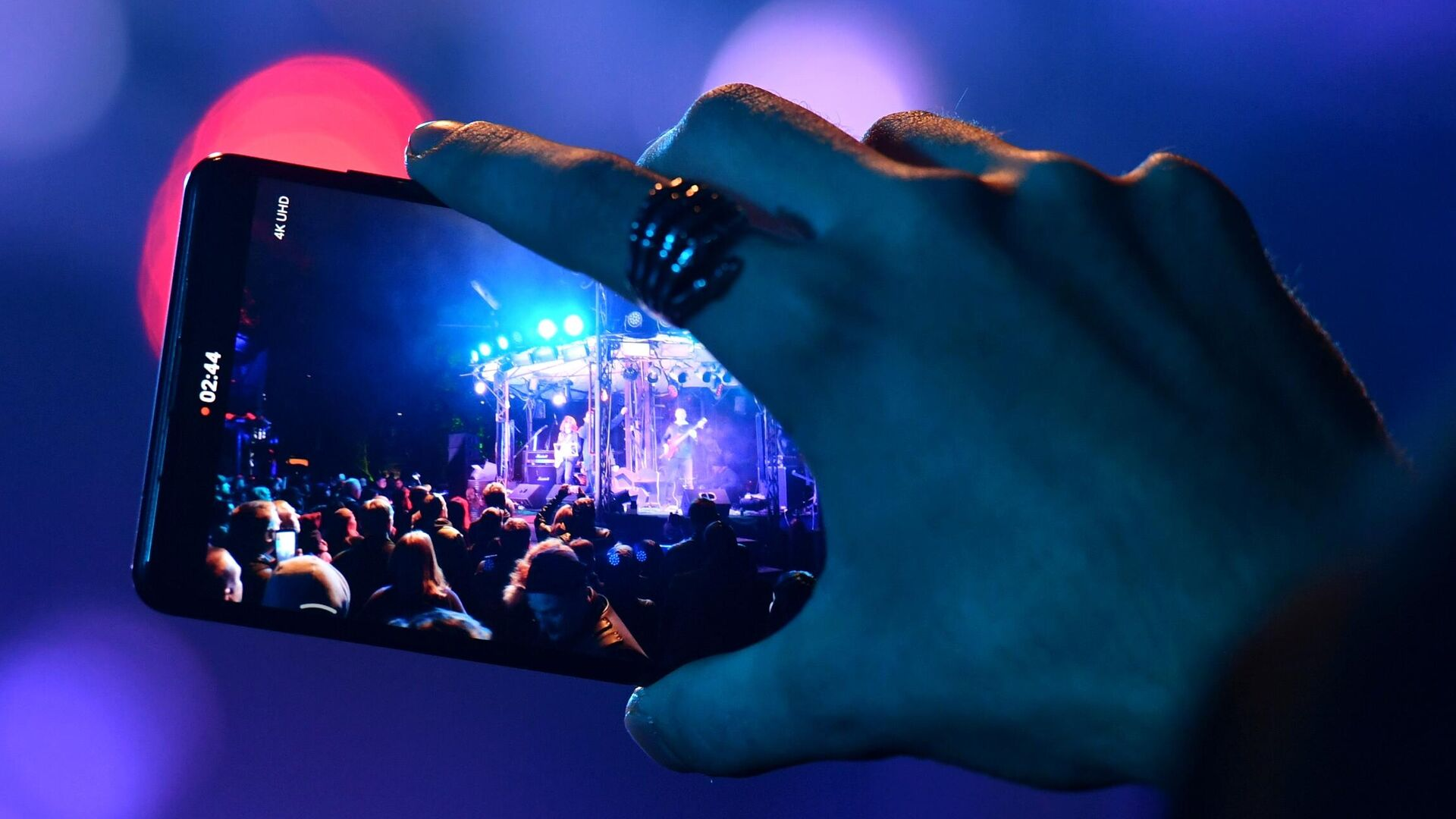 Зритель снимает на мобильный телефон выступление музыкантов на концерте - РИА Новости, 1920, 08.02.2021