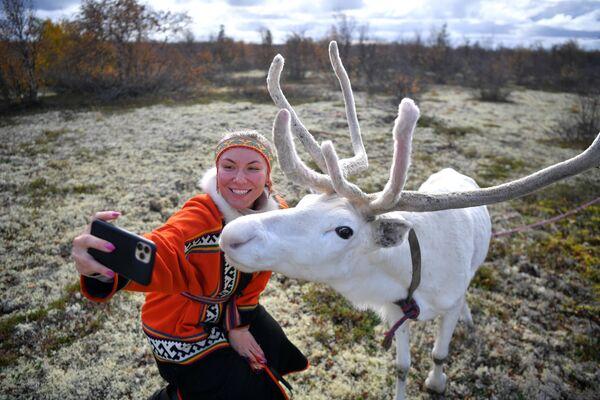Девушка фотографируется с северным оленем на территории Центра арктического туризма в Ненецком автономном округе
