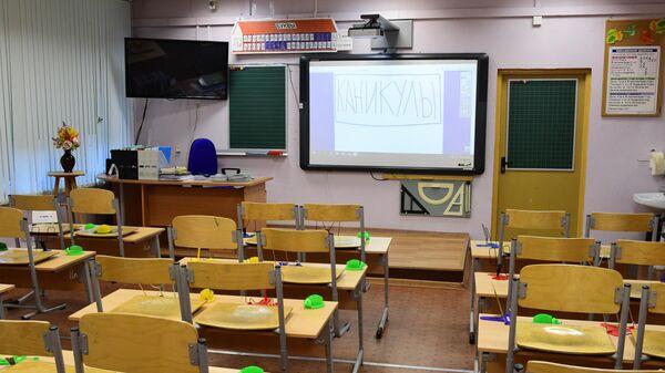 Надпись Каникулы на мониторе в учебном классе в московской школе