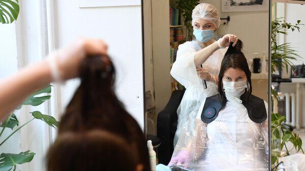 Мастер в защитной маске делает стрижку посетителю салона красоты