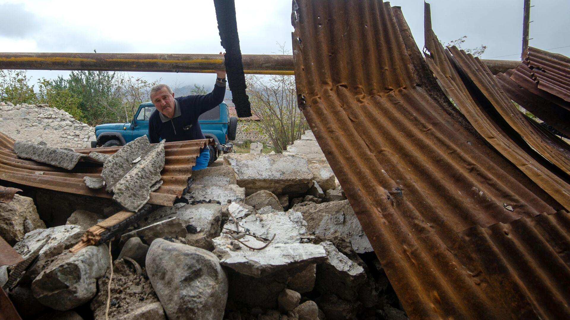 Мужчина у хозяйственной постройки, разрушенной в результате обстрела общины Иванян Нагорного Карабаха - РИА Новости, 1920, 02.10.2020