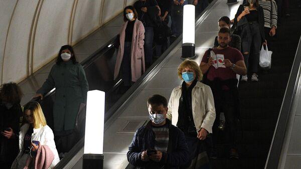 Пассажиры спускаются по эскалатору на станции метро Парк культуры в Москве