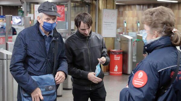 Пассажиры в вестибюле станции метро Пражская в Москве, где проводится проверка масочного режима