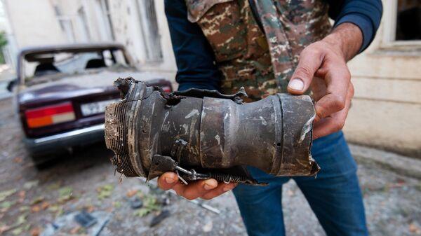 Мужчина держит в руках осколок от разорвавшегося снаряда в результате обстрела на одной из улиц города Мартуни