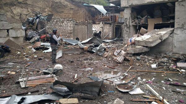 Журналист снимает дом, поврежденный в результате обстрелов Степанакерта