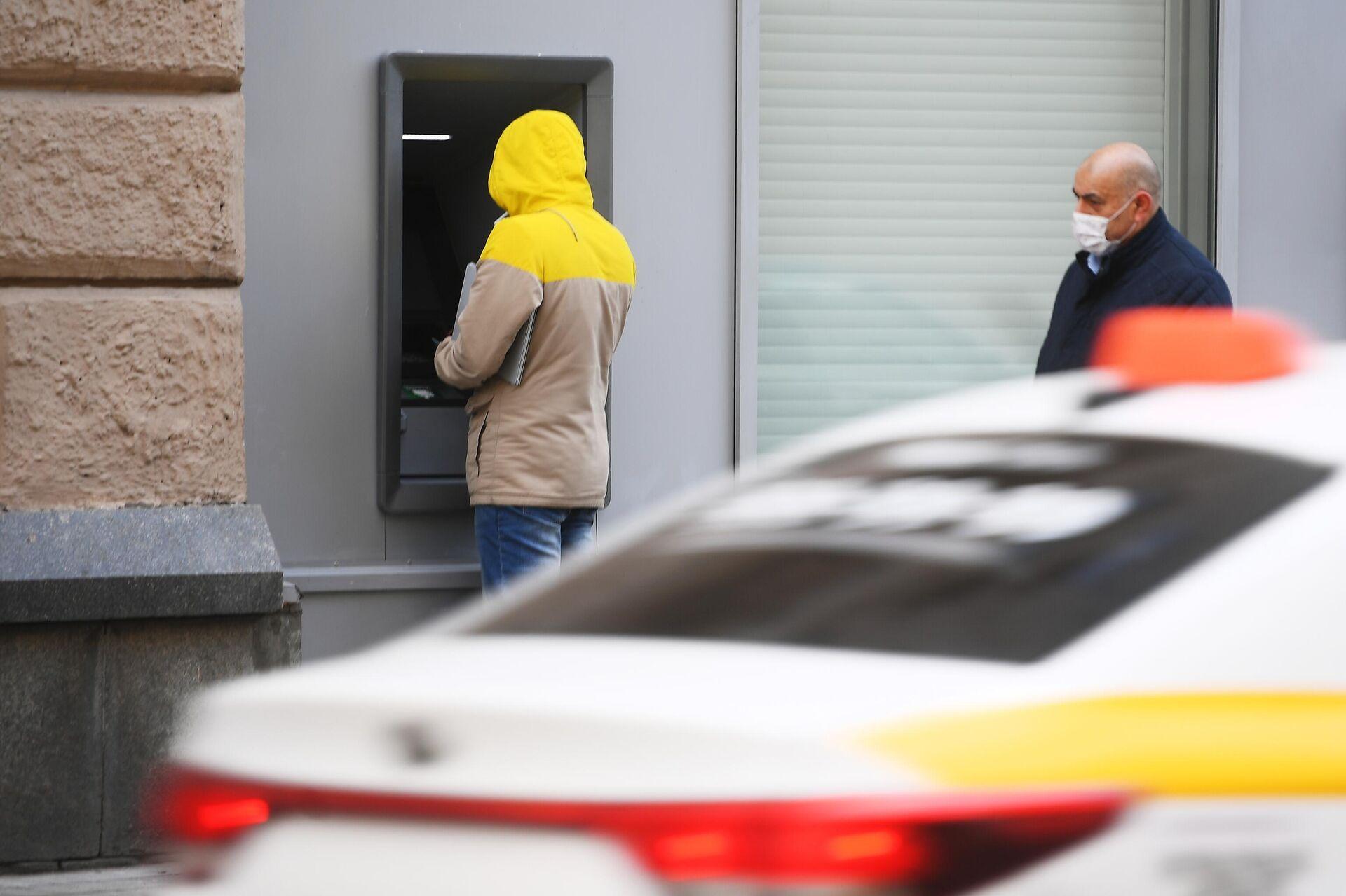 Мужчина у банкомата и прохожий в защитной маске - РИА Новости, 1920, 08.09.2021