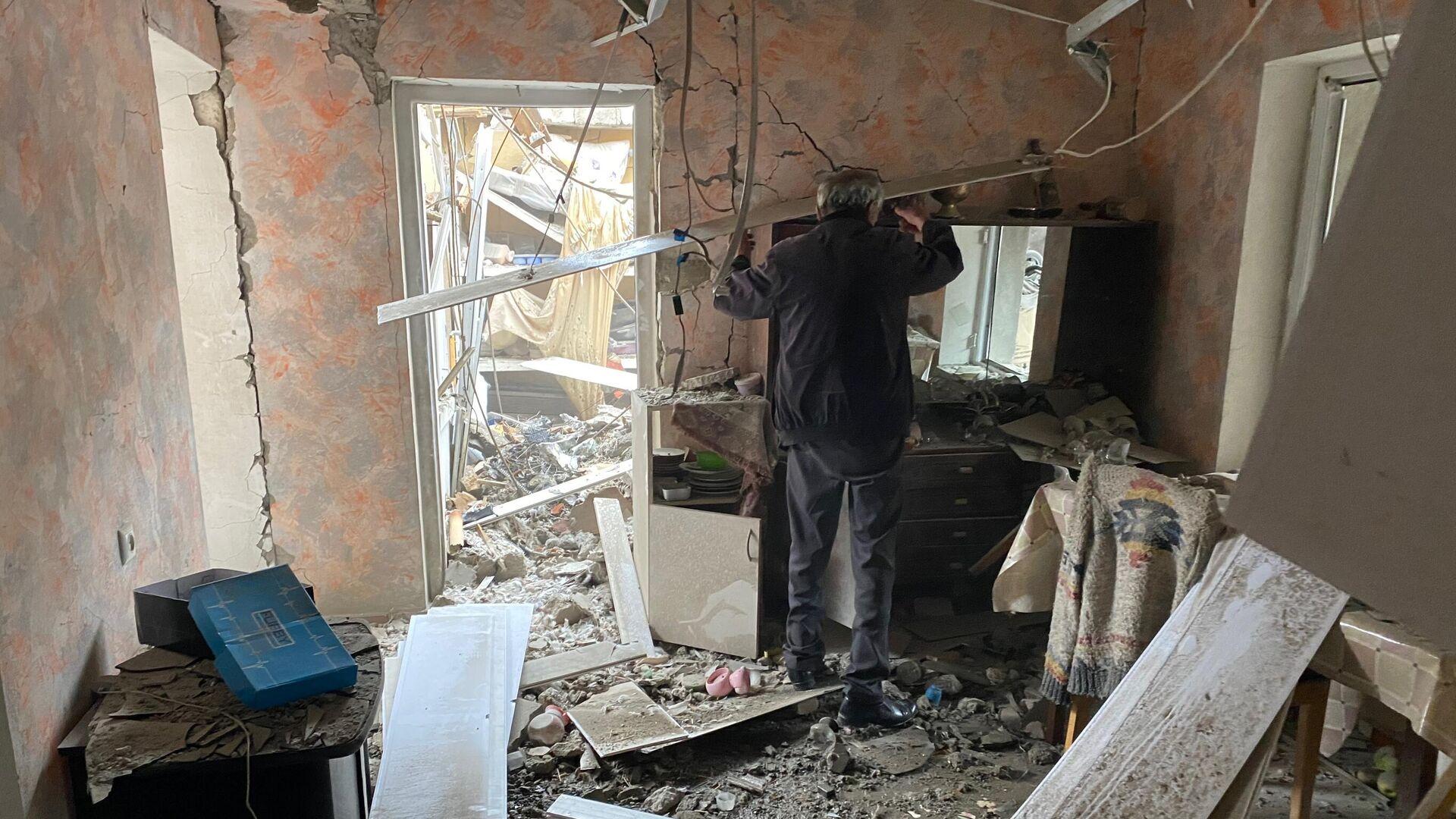 Мужчина осматривает комнату дома в Степанакерте, разрушенного после обстрела - РИА Новости, 1920, 11.10.2020