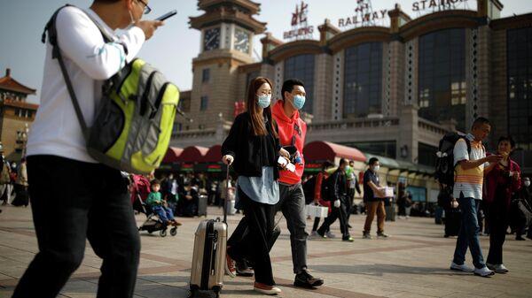 Люди с защитных масках возле железнодорожного вокзала в Пекине