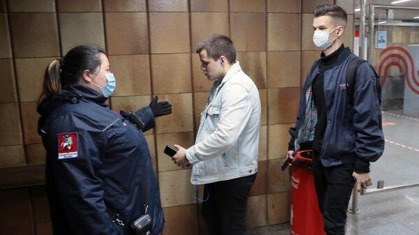 Пассажиры на станции метро Пражская в Москве, где проводится проверка масочного режима