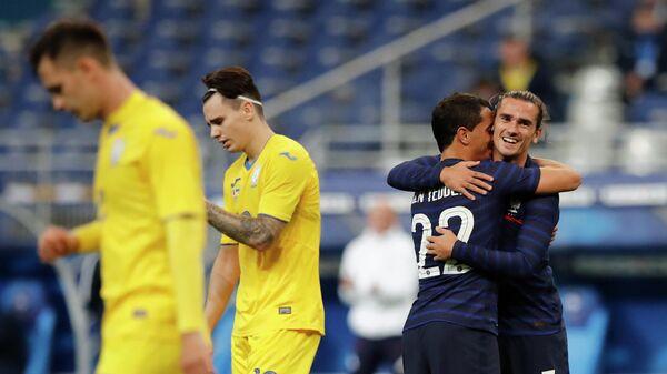 Футболист сборной Франции Антуан Гризманн (справа) радуется забитому голу в товарищеском матче против команды Украины