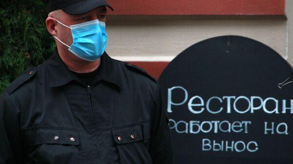 Сотрудник охраны в медицинской маске на улице Арбат в Москве