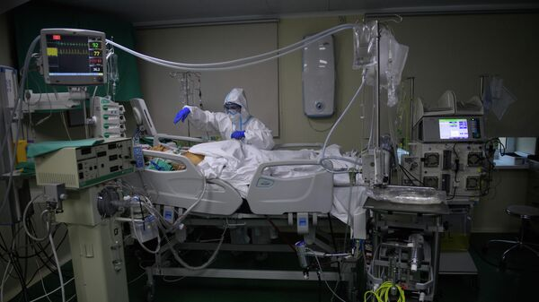 Медицинский работник оказывает помощь пациенту с COVID-19 в отделении реанимации и интенсивной терапии городской клинической больнице № 52