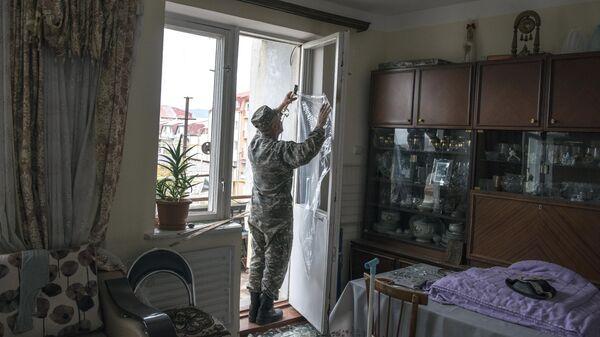 Мужчина закрывает полиэтиленовой пленкой окно с выбитыми стеклами после обстрелов Степанакерта Нагорном Карабахе