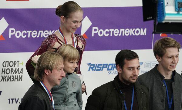 Александра Трусова (в центре на втором плане), Евгений Плющенко с сыном Александром (слева на первом плане)