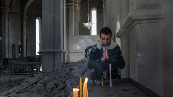 Местный житель в разрушенной обстрелом церкви в городе Шуши. Город Шуши в Карабахе подвергся обстрелу