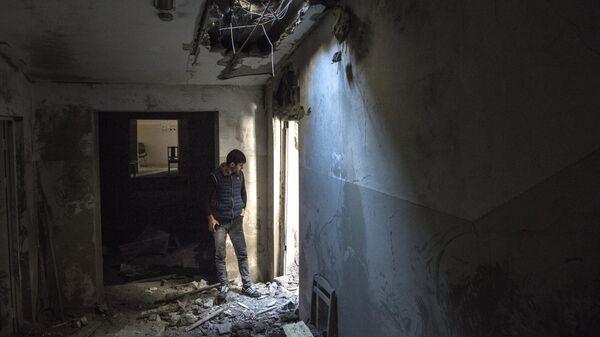 Местный житель в разрушенном доме в городе Шуши