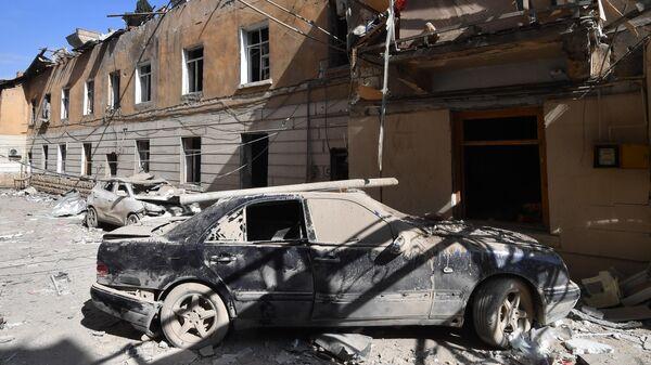 Искореженный автомобиль у жилого дома, разрушенного в результате ракетного обстрела города Гянджа