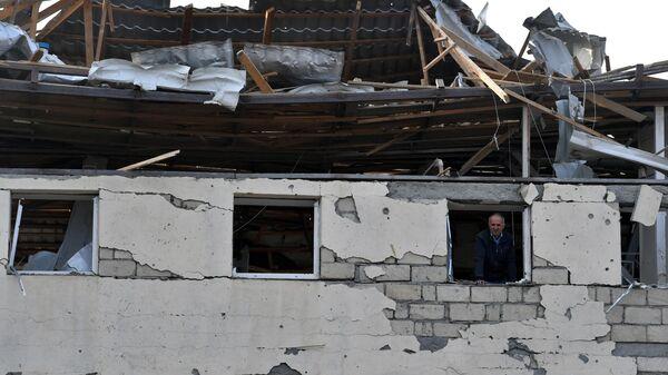 Житель в окне жилого дома, разрушенного в результате ракетного обстрела города Гянджа