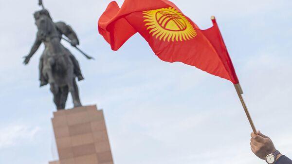 Флаг Киргизии в руке участника митинга в Бишкеке