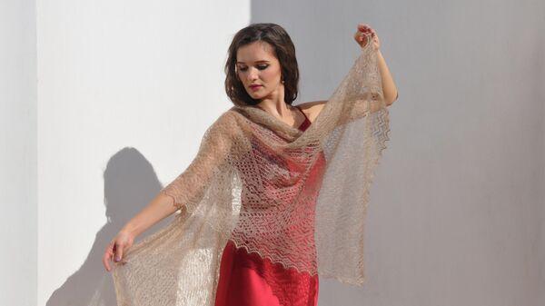 Модель демонстрирует оренбургский пуховой платок