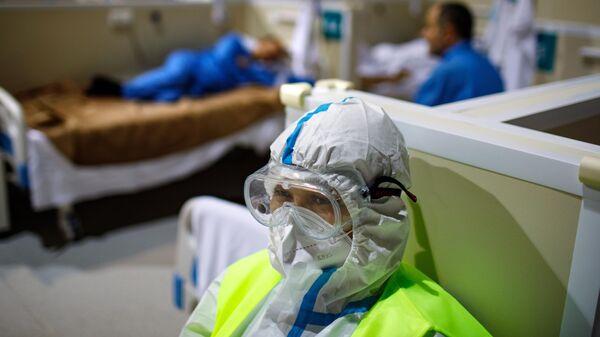 Медицинский работник и пациенты во временном госпитале для пациентов с COVID-19 в ледовом дворце Крылатское