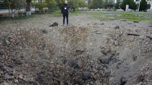 Мужчина возле воронки от упавшего снаряда возле здания школы №10 в Степанакерте