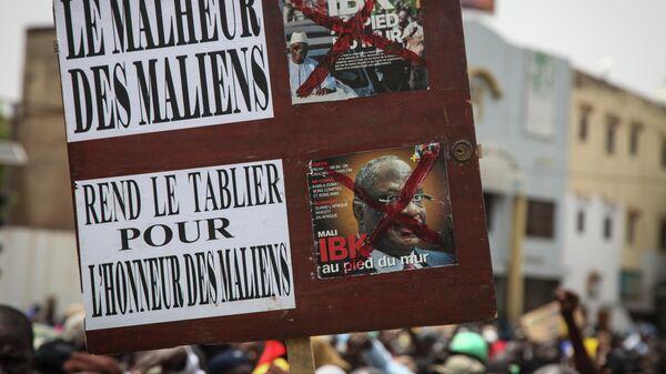 Участники акции протеста в Мали держат плакат с надписью Беда малийцев. Уступите во имя чести малийцев